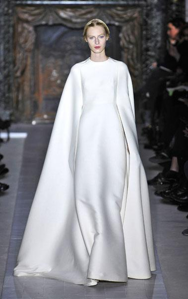 <b>Valentino SS13 </b><br><br>Models' bodies were completely covered up in full-length white gowns that featured cape-like arms.<br><br>© Rex