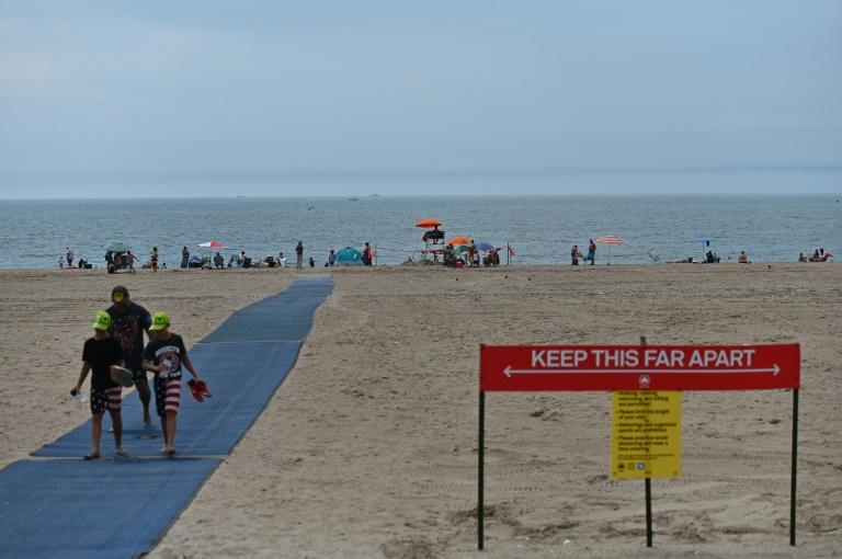The Coney Island beach in New York City may be open, but the sign makes it clear how far away you should stay from people to remain safe from COVID-19 (AFP Photo/Angela Weiss)