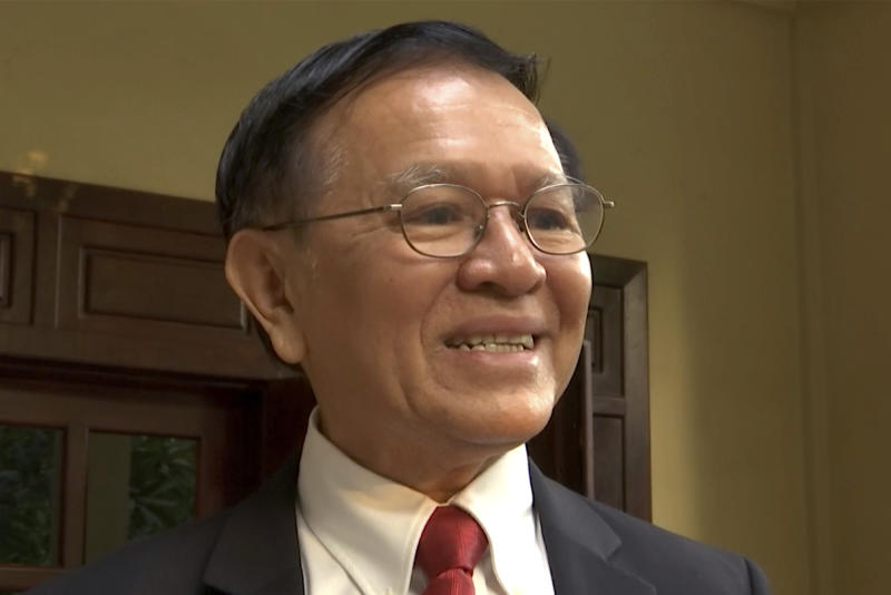 In this image made from video, Cambodia's opposition leader Kem Sokha speaks to the media on steps of his home before leaving for his trial in Phnoem Penh, Wednesday, Jan. 15, 2020. The trial of the top Cambodian opposition leader charged with treason began Wednesday, more than two years after he was arrested in what is widely seen as a politically motivated prosecution. (APTN via AP)