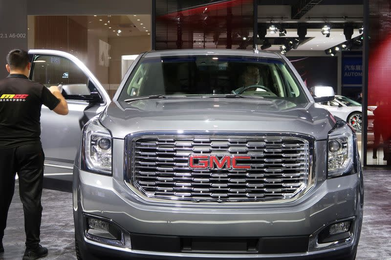 FILE PHOTO: Staff member cleans a General Motors Company (GMC) vehicle displayed at the second China International Import Expo (CIIE) in Shanghai