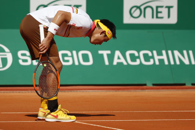 Japan's Kei Nishikori checks the line to determine whether to ball was in or out during the men's singles final match of the Monte Carlo Tennis Masters tournament against Spain's Rafael Nadal in Monaco, Sunday April 22, 2018. (AP Photo/Christophe Ena)