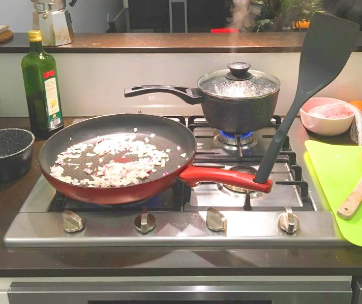 Spatula Hack in red pan on stove cooking onion