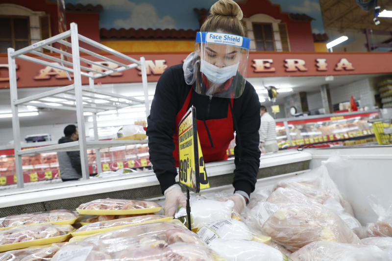 Amid concerns of the spread of COVID-19, a worker stocks poultry at El Rancho grocery store in Dallas, Monday, April 13, 2020. (AP Photo/LM Otero)