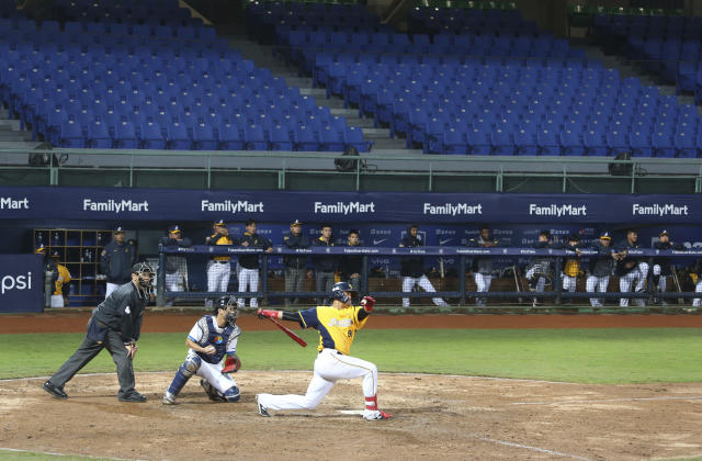 Players of Chinese Professional Baseball League play baseball with no audience at Xinzhuang Baseball Stadium in New Taipei City, Taiwan, Friday, April 24, 2020. Taiwan's five-team Chinese Professional Baseball League is barring spectators over concerns they would spread the deadly coronavirus, meaning games are played with plastic seats void of fans.(AP Photo/Chiang Ying-ying)