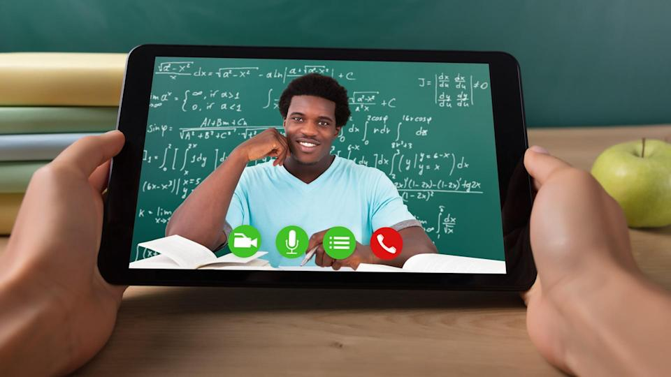 Close-up Of A Student's Hand Video Conferencing With Happy Male Teacher On Digital Tablet.