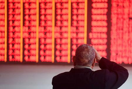 Man sits in front of an electronic board showing stock information at a brokerage house in Hangzhou