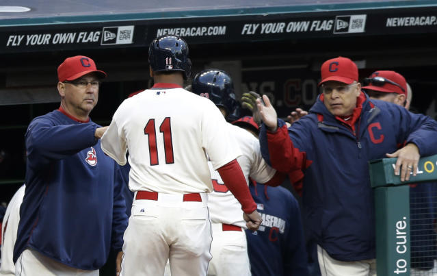 Cleveland Indians' Jose Ramirez, center, is congratulated by manager Terry Francona, left, and teammates after scoring on a sacrifice fly by Nick Swisher in the fifth inning of a baseball game against the Chicago White Sox, Saturday, May 3, 2014, in Cleveland. (AP Photo/Tony Dejak)