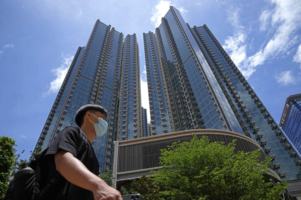 In this Tuesday, June 15, 2021, photo, a man walks in front of the Grand Central residential building complex where one of the HK$10.8 million (US$1.4 million) 449 square feet single-room flats will be offered as a prize in a lucky draw. Coronavirus vaccine incentives offered by Hong Kong companies, including a lucky draw for an apartment, a Tesla car and even gold bars, are helping boost the city's sluggish inoculation rate. (AP Photo/Kin Cheung)