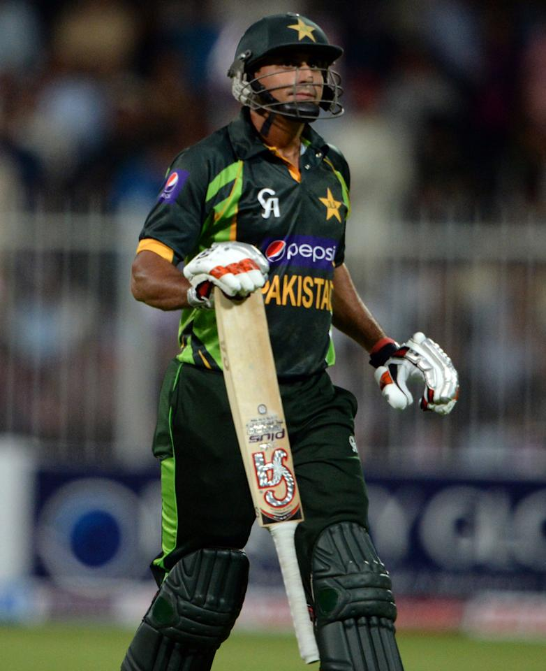 Pakistan's cricketer Nasir Jamshed walks back to the pavilion after he was caught out by South African cricketer David Miller (unseen) during the first one-day in Sharjah Cricket Stadium in Sharjah on October 30, 2013. South African captain AB de Villiers won the toss and decided to bat in the first of five one-day internationals against Pakistan in Sharjah. AFP PHOTO/ ASIF HASSAN        (Photo credit should read ASIF HASSAN/AFP/Getty Images)