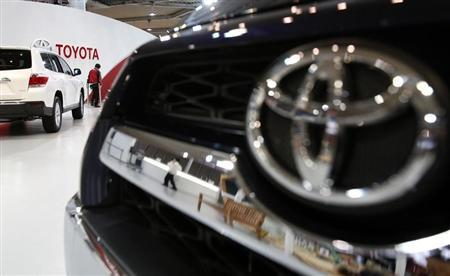 A showroom staff member works under the logo of Toyota Motor Corp, between cars displayed at its showroom in Tokyo