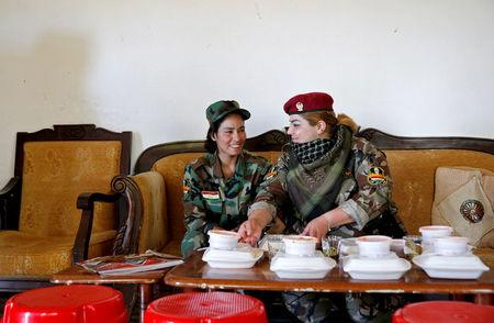 Iraqi Kurdish female fighter Haseba Nauzad (R), 24, and Yazidi female fighter Asema Dahir, 21, sit together to have their lunch at a site near the frontline of the fight against Islamic State militants in Nawaran near Mosul, Iraq, April 20, 2016. REUTERS/Ahmed Jadallah