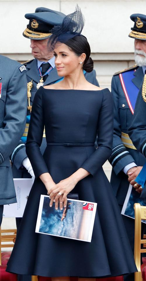 """<p>Since joining forces with Givenchy's artistic director Clare Waight Keller for her royal wedding gown, Markle has seemingly taken a few <a href=""""https://www.elle.com/culture/celebrities/g22126994/meghan-markle-audrey-hepburn-style/"""" target=""""_blank"""">style notes from famous Givenchy muse</a>, Audrey Hepburn. For the Royal Air Force's 100th anniversary celebration, Markle wore a navy fit-and-flare dress with a boatneck neckline, reminiscent of the black cocktail dress Hepburn wore in <em>Sabrina.</em></p>"""