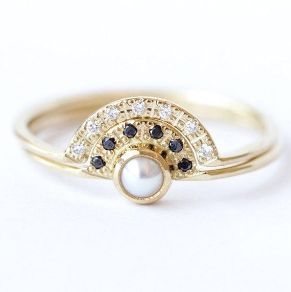 """<p>For bohemian brides, this <span>Wedding Ring Set</span> ($1,281) features a pearl engagement ring with black diamonds and a pavé diamond <a class=""""link rapid-noclick-resp"""" href=""""https://www.popsugar.com/Wedding"""" rel=""""nofollow noopener"""" target=""""_blank"""" data-ylk=""""slk:wedding"""">wedding</a> ring. How pretty!</p>"""