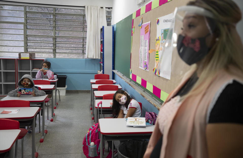 A teacher works with students, all of them wearing masks, on the first day back to in-person classes amid the COVID-19 pandemic at the Raul Antonio Fragoso public school in Sao Paulo, Brazil, Monday, Feb. 8, 2021. Sao Paulo state government has allowed the schools to resume classes with up to 35% of its students. (AP Photo/Andre Penner)