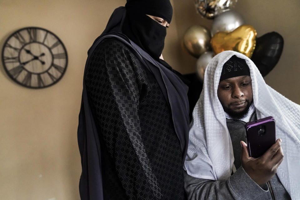Myon Burrell watches a video of protestors chanting his name during a Black Lives Matter rally that his wife, Lacretia Luckett, left, attended earlier in the year, Thursday, Dec. 17, 2020, at their home in Minneapolis. Two days earlier, Burrell was released from prison after Minnesota's pardon board commuted his sentence in a high-profile murder case that raised questions about the integrity of the criminal justice system. (AP Photo/John Minchillo)