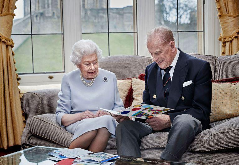 <p>The royal couple smiles at a card made by the Cambridge children in a portrait taken for their 73rd wedding anniversary. </p>