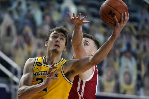 Michigan guard Franz Wagner (21) makes a layup as Wisconsin forward Micah Potter (11) defends during the second half of an NCAA college basketball game Tuesday, Jan. 12, 2021, in Ann Arbor, Mich. (AP Photo/Carlos Osorio)