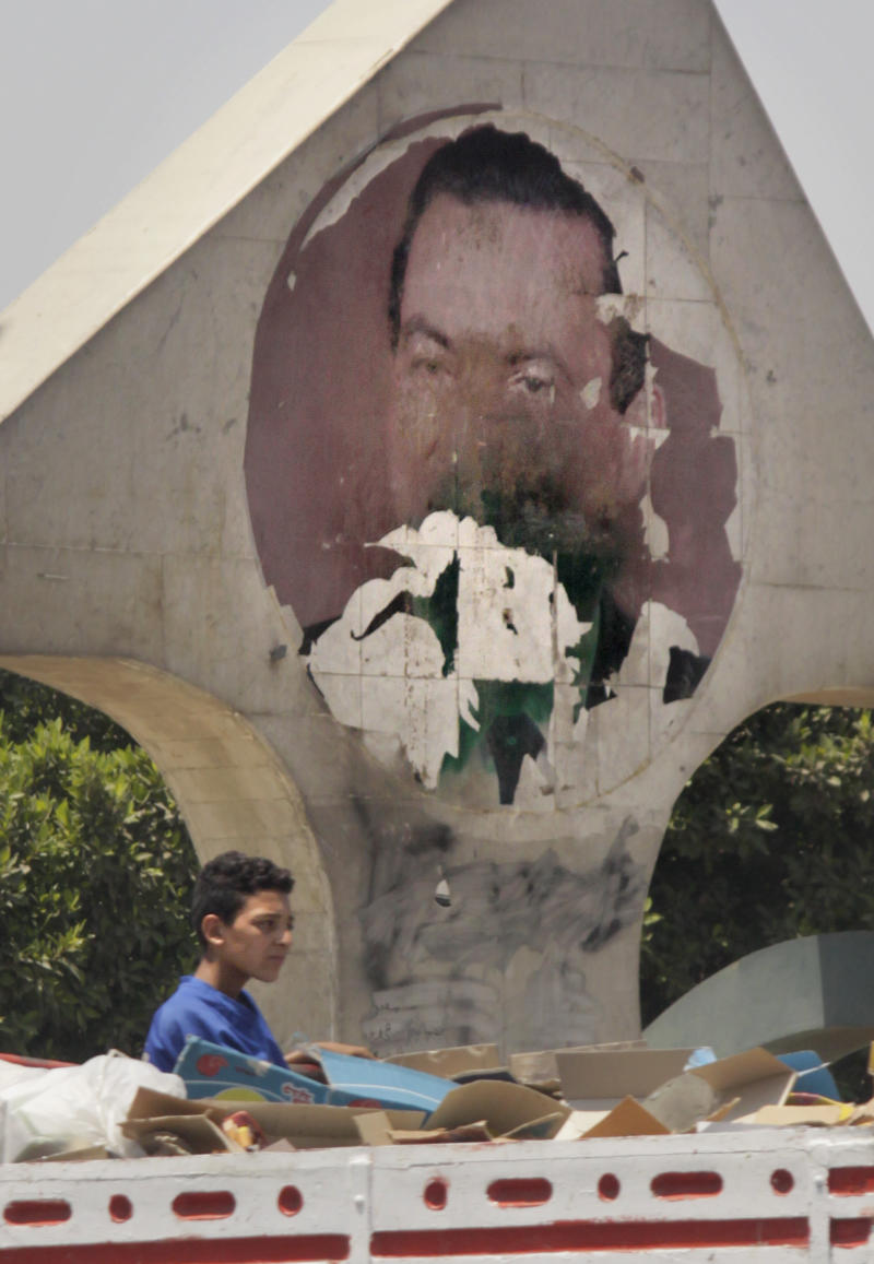 An Egyptian worker on a truck passes by a defaced ceramic image of ousted Egyptian President Hosni Mubarak, in Cairo, Egypt, Saturday, July 16, 2011. Hundreds of Egyptians have set up protest tent camps in the main city square and vowed they would not leave until Egypt's temporary military rulers purge the remnants of Hosni Mubarak's deposed regime.  (AP Photo/Amr Nabil)