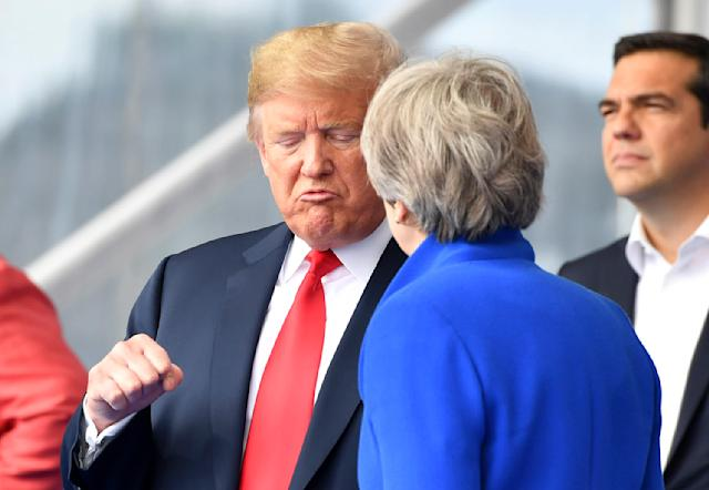 <p>President Trump clenches a fist when talking to British Prime Minister Theresa May during a summit of heads of state at NATO headquarters in Brussels on Wednesday, July 11, 2018. NATO leaders gathered in Brussels for a two-day summit to discuss Russia, Iraq and their mission in Afghanistan. (Photo: Geert Vanden Wijngaert/AP) </p>