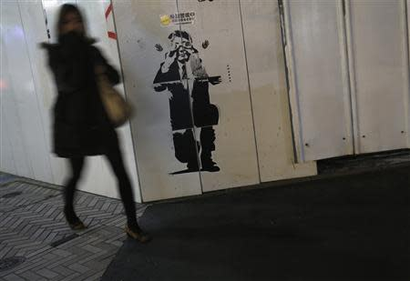 A pedestrian walks past a sticker art made by an artist known as 281 Antinuke, designed in the likeness of Japan's Prime Minister Shinzo Abe, along a street in Tokyo November 26, 2013. REUTERS/Yuya Shino
