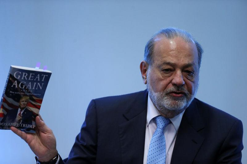 Mexican billionaire Carlos Slim shows the book Crippled America: How to make America great again by Donald Trump during a news conference in Mexico City