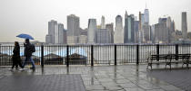 Visitors walk along Brooklyn Heights Promenade during a rainy day Friday April 5, 2019, in New York. The promenade makes up the top deck overhang of a deteriorating Brooklyn-Queens Expressway and the city's plans for repairs has drawn neighborhood protest, since it calls for a temporary six lane highway on the promenade. (AP Photo/Bebeto Matthews)