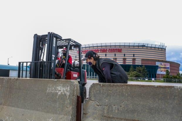 Workers wear masks outside the Canadian Tire Centre in Ottawa on Sept. 24, 2021.  (Stu Mills/CBC - image credit)