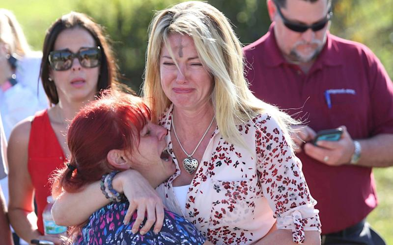 Parents wait for news after a reports of a shooting at Marjory Stoneman Douglas High School in Parkland, Florida - FR170673 AP