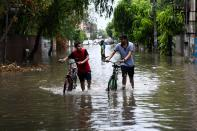 Youths push thir bicycles along a water-logged street following heavy rains in Amritsar on July 19, 2020. (Photo by NARINDER NANU / AFP) (Photo by NARINDER NANU/AFP via Getty Images)