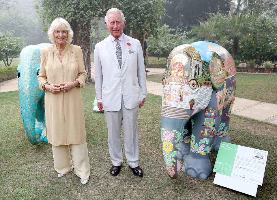NEW DELHI, INDIA - NOVEMBER 08:  Camilla, Duchess of Cornwall and Prince Charles, Prince of Wales pose with two of the 101 painted sculptures, named after the 101 elephant corridors that have been mapped across the country, at an