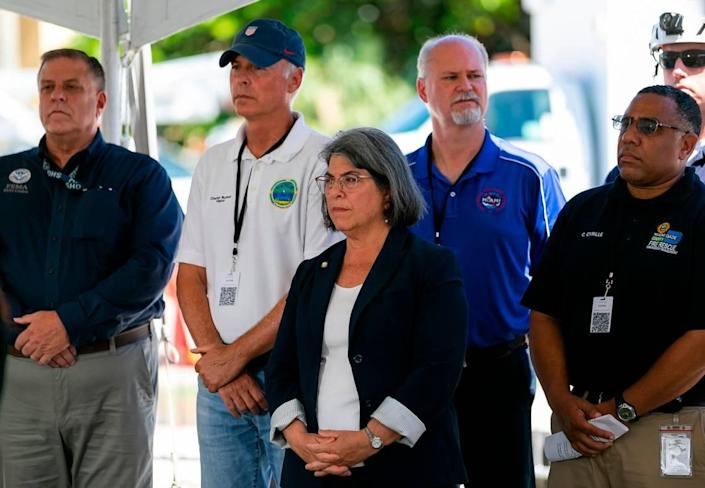 Miami-Dade County Mayor Daniella Levine Cava, center, listens as Florida Gov. Ron DeSantis speaks during a press conference near the Champlain Towers South collapse site in Surfside, Florida, on Saturday, July 3, 2021.
