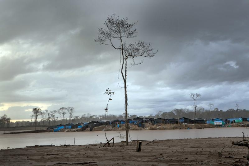 In this May 4, 2014 photo, a mining camp lines the horizon in La Pampa in Peru's Madre de Dios region. Since artisanal gold mining took hold in La Pampa, miners began carving a lawless, series of ramshackle settlement out of the Amazonian jungle territory in 2008. The artisanal miners, who know they will be soon be evicted, are working up to the last minute after Peru's government declared all informal mining illegal on April 19. (AP Photo/Rodrigo Abd)