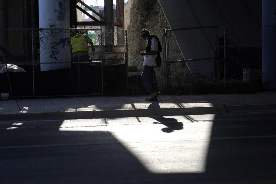 A pedestrian walks underneath the Interstate 395 overpass as a crew works on the new Signature Bridge, Tuesday, April 27, 2021, in the Overtown neighborhood in Miami. The bridge was built in the 1960's which forced out thousands of residents. (AP Photo/Lynne Sladky)
