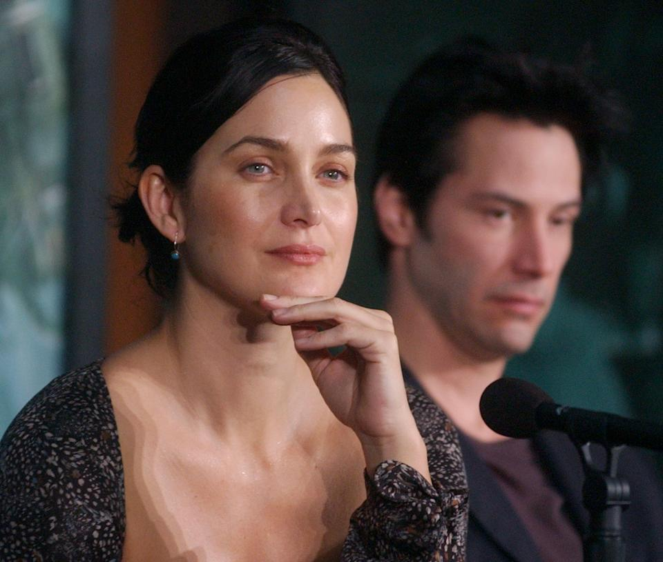 Cast members Carrie-Ann Moss (L) and Keanu Reeves speak with reporters during a news conference to promote the sci-fi action thriller motion picture