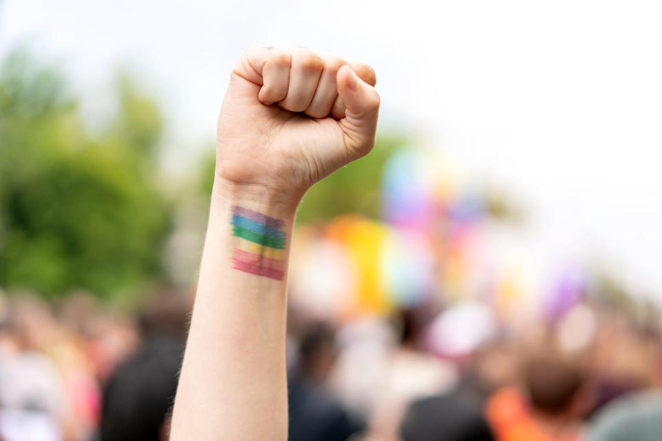 A raised hand in the air forming a fist with the pride flag during a parade