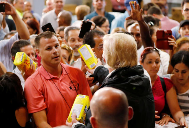 <p>President Donald Trump hands out bags of rice to a crowd of local residents affected by Hurricane Maria as he visits a disaster relief distribution center at Calgary Chapel in San Juan, Puerto Rico, Oct. 3, 2017. (Photo: Jonathan Ernst/Reuters) </p>