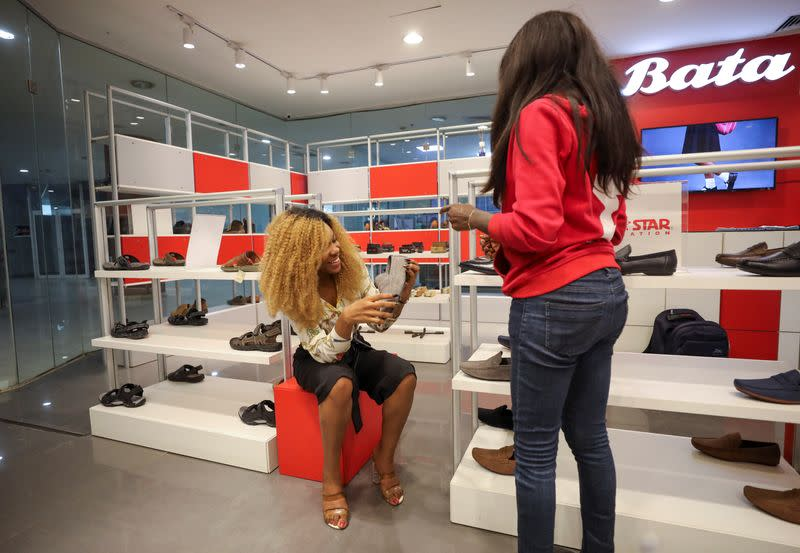 A customer smiles while looking at a shoe inside a Bata store in Abuja
