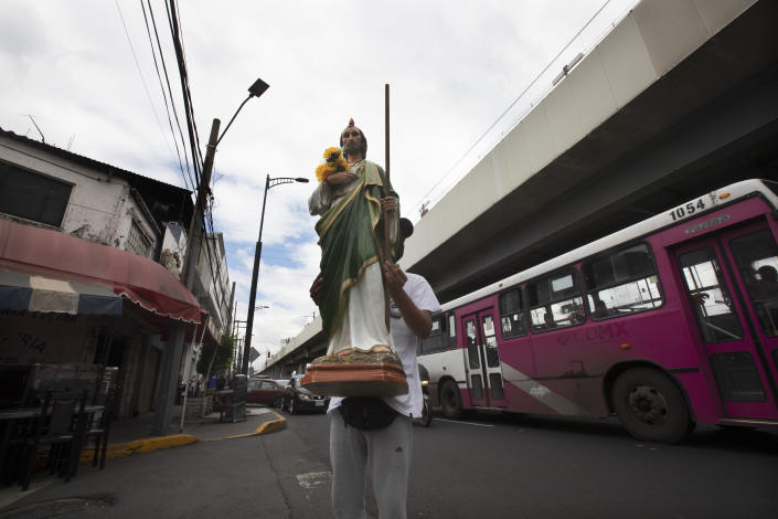 A devotee seeking alms holds a statue of Saint Judas near the site where an elevated section of the subway Line 12 collapsed in early May killing 26 people, in Mexico City, Thursday, June 17, 2021. Residents who once depended on Line 12 are now obligated to find an alternative way to commute. (AP Photo/Marco Ugarte)