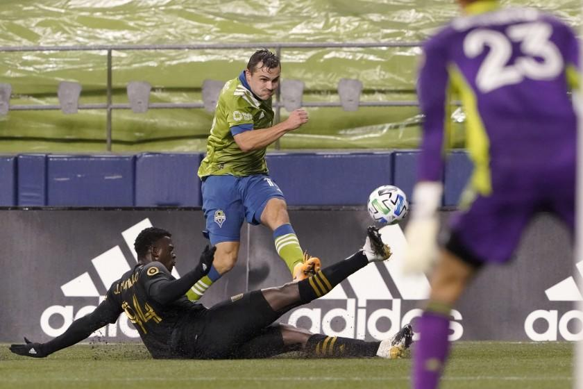 Los Angeles FC defender Jesus David Murillo, left, slides across on a tackle attempt on Seattle Sounders.