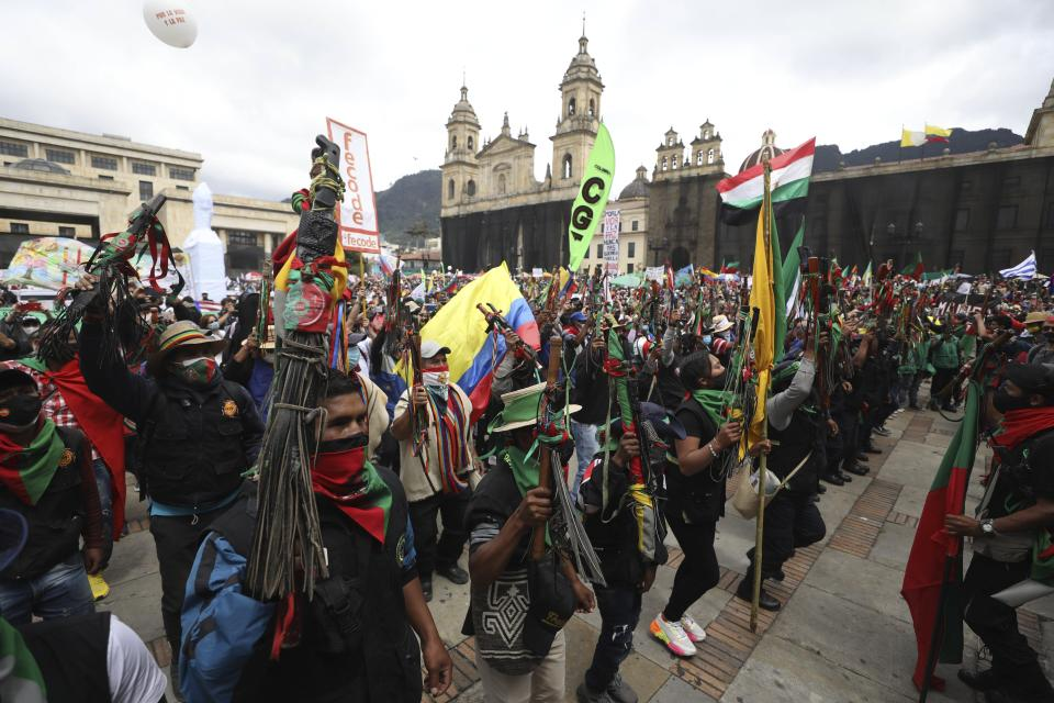 Members of the Indigenous Guard shout slogans against the government during a national strike in Bogota, Colombia, Wednesday, Oct. 21, 2020. Workers' unions, university students, human rights defenders, and Indigenous communities have gathered for a day of protest in conjunction with a national strike across Colombia. The protest is against the assassinations of social leaders, in defense of the right to protest and to demand advances in health, income and employment. (AP Photo/Fernando Vergara)