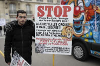 """A circus worker holds a poster to defend the circus business during a protest Tuesday, Jan.26, 2021. French lawmakers start debating Tuesday a bill that would ban using wild animals in traveling circuses and keeping dolphins and whales in captivity in marine parks, amid other measures to better protect animal welfare. Circus workers stage a protest outside the National Assembly to denounce what they consider """"a mistake."""" (AP Photo/Lewis Joly)"""