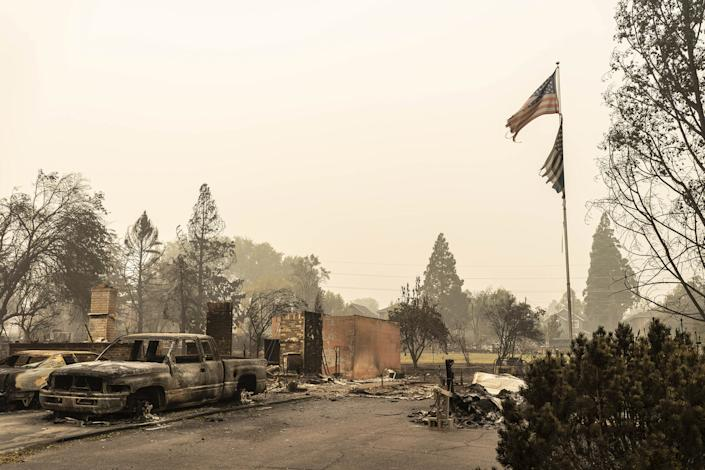 "A U.S. flag flies at a burnt home in a neighborhood destroyed by wildfire on Sept. 13 in Talent, OR <span class=""copyright"">David Ryder—Getty Images</span>"