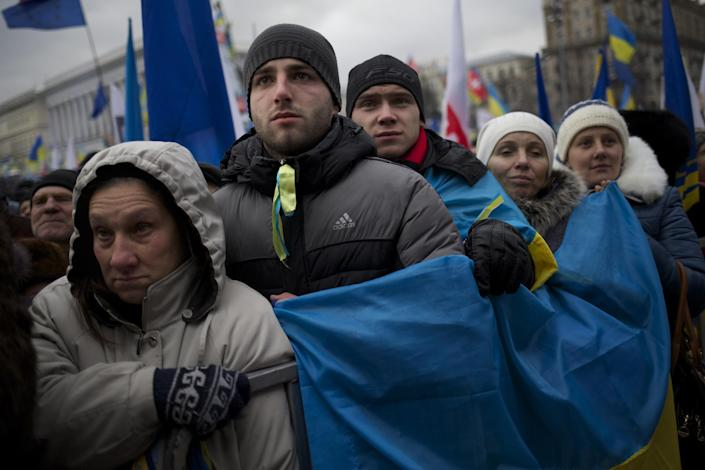 Pro-European Union activists hold a Ukrainian national flag as they listen to an orator during a rally in the Independence Square in Kiev, Ukraine, Sunday, Dec. 8, 2013. Hundreds of thousands of Ukrainians rallied in the center of Kiev on Sunday in the biggest protest since 2004's pro-democracy Orange Revolution, denouncing President Viktor Yanukovych's decision to turn away from Europe and raising the stakes in a tense political standoff gripping this ex-Soviet republic. (AP Photo/Alexander Zemlianichenko)