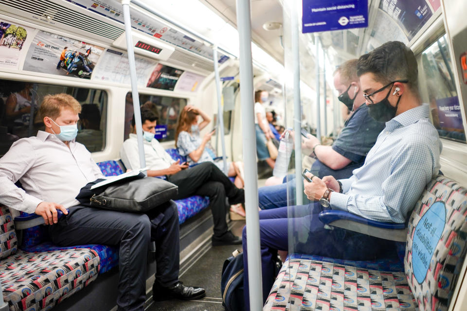 People sit on an Underground train, in London, Monday, July 19, 2021. As of Monday, face masks are no longer legally required in England, and with social distancing rules shelved, there are no limits on the number of people attending theater performances or big events. (AP Photo/Alberto Pezzali)