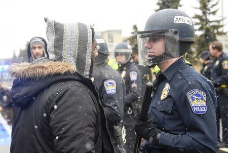 A member of the Black Lives Matter protesters argues with a police officer as they shut down the main road to the Minneapolis St. Paul Airport following a protest at the Mall of America in Bloomington, Minnesota December 23, 2015. REUTERS/Craig Lassig