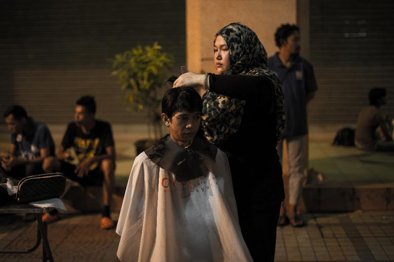 Stylist Azmina Burhan cuts the hair of a homeless person in downtown Kuala Lumpur, on November 13, 2013