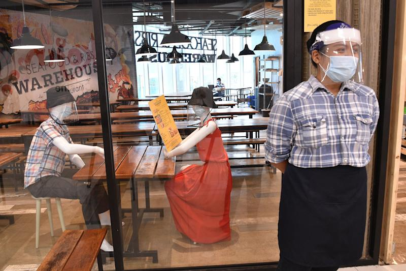 A staff member of a restaurant stands near mannequins wearing face masks and face shields displayed inside a restaurant, to simulate seating arrangements when restaurants will be allowed to once again cater to dine-in customers, in a mall in Manila on June 2, 2020. (Photo: TED ALJIBE/AFP via Getty Images)