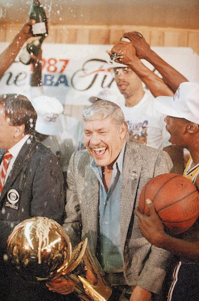 FILE - In this June 15, 1987 file photo, Los Angeles Lakers owner Jerry Buss gets doused with champagne from members of his team as he holds the NBA Championship trophy after the Lakers defeated the Boston Celtics 106-93 to win the NBA Championship four games to two in Inglewood, Calif. Buss, the Lakers' playboy owner who shepherded the NBA franchise to 10 championships, has died. He was 79. Bob Steiner, an assistant to Buss, confirmed Monday, Feb. 18, 2013 that Buss had died in Los Angeles. Further details were not available. (AP Photo/Lennox Mclendon, File)
