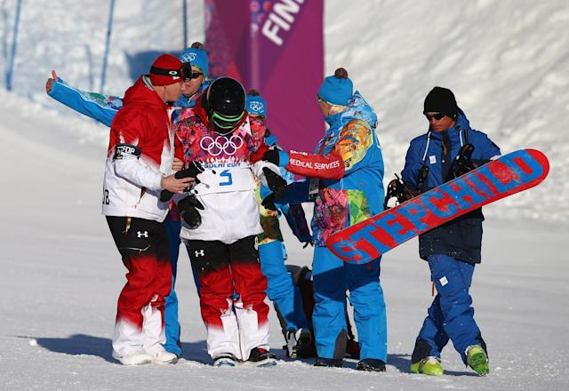 SOCHI, RUSSIA - FEBRUARY 08: Charles Reid of Canada is helped after crashing out during the Snowboard Men's Slopestyle Semifinals during day 1 of the Sochi 2014 Winter Olympics at Rosa Khutor Extreme Park on February 8, 2014 in Sochi, Russia. (Photo by Ryan Pierse/Getty Images)