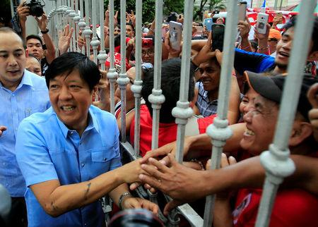 """Former senator Ferdinand """"Bongbong"""" Marcos Jr and son of late former dictator Ferdinand Marcos is greeted by his supporters upon his arrival at the Supreme Court in metro Manila"""